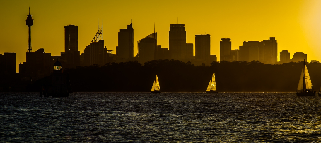 Racing home: A view of the Sydney skyline at dusk. Yachts are just finishing their race, their sails catching the setting sun.