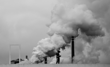 Smoke may get in your eyes...: A view in northern Spain of factory smoke and an engineer in the foreground